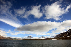 Puffy white clouds, blue sky, mountain peaks and glaciers in the arctic Svalbard Stock Photo