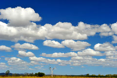 Puffy white clouds & blue sky over remote australian outback, no. Perfectly clear blue sky with puffy white clouds lay over remote barren australian outback Stock Photo