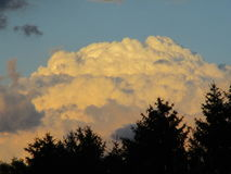 Puffy White Clouds. A burst of puffy white clouds billow atop the ridge Stock Image