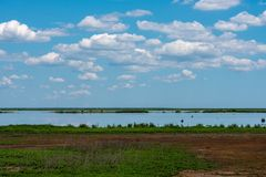 Puffy White Clouds Over a Marsh. Puffy Wwite clouds in a blue sky hover over Marshlands with deep green grasses Royalty Free Stock Photos