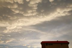 Puffy Yellow Clouds over Condo. Puffy yellowish-white clouds appear as cotton balls as they hang in the sky above a condominium in Pompano Beach, Florida after Stock Photo