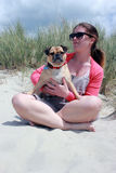 Pug Dog and owner on a sunny beach portrait Stock Image