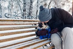 Pug dog sitting on bench with his master. Puppy wearing winter coat. Man hugging his pet in winter park. Best friend stock photo