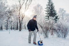 Pug dog walking on snow with his master in park. Puppy wearing winter coat. Clothes for animals stock photos