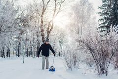 Pug dog walking on snow with his master in park. Puppy wearing winter coat. Clothes for animals royalty free stock photos