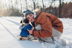 Pug dog walking on snow with his master. Puppy wearing winter coat. Man hugging his pet in winter forest. Clothes for animals stock images