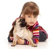 Pug-Hund, der die Backe des kleinen Mädchens bitting ist Stockbild