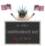 Pug puppy dog with American flag and statue of liberty crown, behind blackboard with text happy 4th of July and independence day Royalty Free Stock Photography
