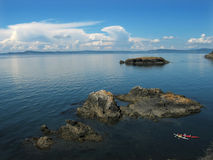 Puget Sound Kayaks Mountains Clouds. A view across Puget Sound from Rosario Beach State Park, Washington. There are rocky islands and two kayaks in the royalty free stock photos