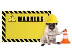 Pughund mit gelbem Erbauerarbeitskraftschutzhelm und leerem Warnzeichen lizenzfreie stockbilder
