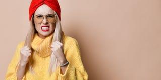 Pugilato aggressivo della donna pronto a combattere emozione di espressione in maglione giallo degli occhiali da sole di modo fotografie stock