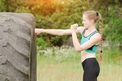 Pugilato della giovane donna con la gomma workout immagine stock