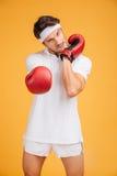 Pugile aggressivo del giovane nello scaldarsi rosso dei guanti fotografia stock libera da diritti