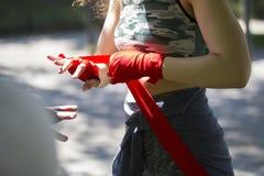 Pugile caucasico atletico della donna che avvolge le mani con le fasciature per l'allenamento nel parco di estate Fotografie Stock Libere da Diritti