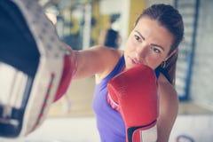Pugile della donna che colpisce il guanto del suo partner di pugilato d'allenamento Immagine Stock Libera da Diritti