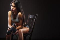 Pugile della donna che si siede sulla sedia Fotografie Stock