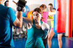 Pugile femminile di scossa con l'addestratore nello sparring Fotografia Stock Libera da Diritti