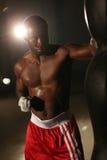 Pugile maschio afroamericano che colpisce la borsa di perforazione negli shorts rossi alla palestra immagine stock