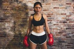 Pugile muscolare femminile di sport con i guantoni da pugile che posano sopra il fondo del mattone della parete immagini stock libere da diritti