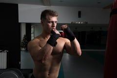 Pugile muscolare senza camicia con il punching ball in palestra fotografia stock