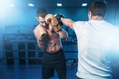 Pugile negli esercizi dei guanti con il partner di pugilato d'allenamento Fotografie Stock