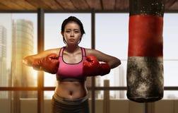 Pugilista asiático bonito da menina que faz o exercício com saco de perfuração Fotos de Stock