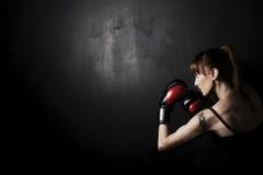 Pugilista da mulher com as luvas vermelhas em Backgound preto Fotografia de Stock Royalty Free