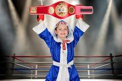 Pugilista do menino que guarda a correia do campeonato no encaixotamento Campeão pequeno As vitórias grandes fotografia de stock