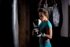 Pugilista fêmea novo em luvas de encaixotamento que treina com punchin do encaixotamento Fotografia de Stock Royalty Free