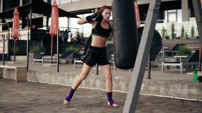 Pugilista fêmea que exercita fora Mulher atlética bonita nas luvas que perfuram um saco fora Auto - conceito da defesa filme