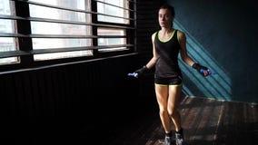 Pugilista fêmea sério novo do movimento lento nas mãos envolvidas aquecer-se, saltando na corda de salto no gym filme