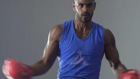Pugilista latino que veste luvas protetoras, sombra que luta no gym, sentido de finalidade filme