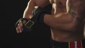 Pugilista masculino rasgado com torso suado que descola envoltórios da mão após a luta foto de stock