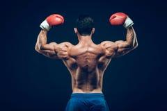 Pugilista muscular no tiro do estúdio, no preto Imagem de Stock