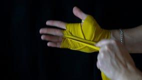Pugilista que envolve as ataduras amarelas do ` s em sua mão antes da luta video estoque