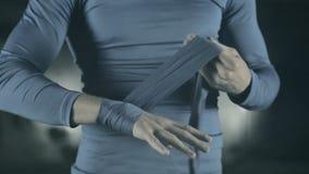 Pugilista que envolve as ataduras em sua mão antes da luta vídeos de arquivo