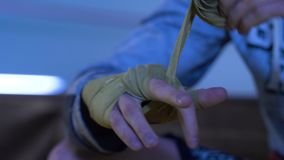 Pugilista que envolve as ataduras em sua mão antes da luta Fim acima O homem amarra suas mãos com uma atadura filme
