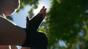 Pugilistas exteriores - muscular e mulher que envolve as mãos com as ataduras para o exercício no dia de verão filme