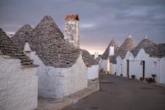 Puglia, Italië Traditionele kegel roofed trullihuizen op een straat in Alberobello Gefotografeerde vroege ochtend met rode hemel royalty-vrije stock foto's