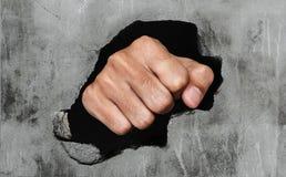 Pugno che tagliato muro di cemento fotografia stock