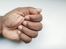 Pugno chiuso di un person& afroamericano x27; mano di s su un fondo bianco fotografia stock