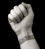Pugno con il tatuaggio della manopola nel reticolo chiave greco sopra priorità bassa nera Fotografie Stock