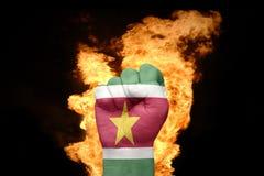 Pugno del fuoco con la bandiera nazionale del Surinam fotografia stock