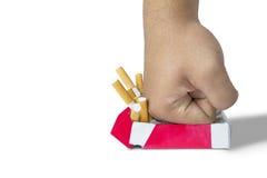 Pugno dell'uomo che schiaccia le sigarette Immagini Stock
