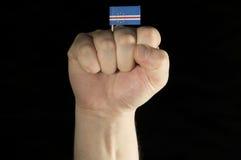 Pugno della mano dell'uomo con la bandiera di Capo Verde isolata sul nero Fotografia Stock Libera da Diritti