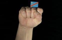 Pugno della mano dell'uomo con la bandiera di Repubblica Democratica del Congo isolata sul nero Fotografie Stock