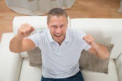 Pugno di serraggio dell'uomo sul sofà Immagini Stock Libere da Diritti