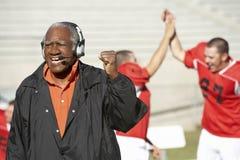 Pugno gridante e di pompaggio dell'allenatore di football americano Fotografie Stock