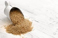 Épuisette de riz brun sur le bois de construction blanc rustique Images stock
