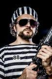 Puissance, concept d'émeute de prison. Homme tenant une mitrailleuse, prisonnier Photographie stock libre de droits